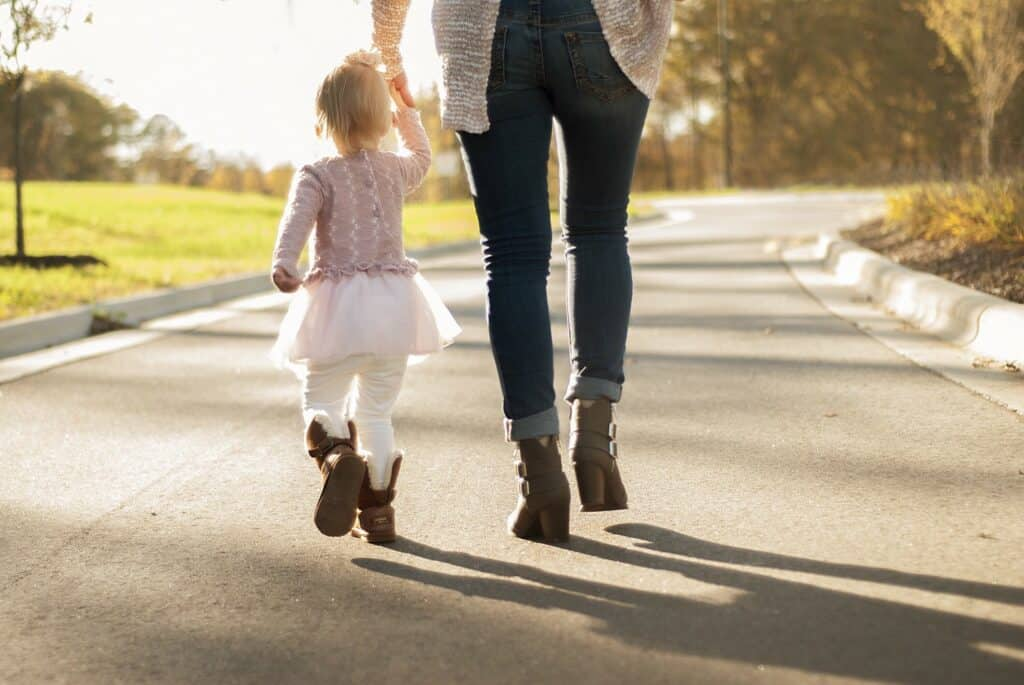 Mother walking with a toddler while holding her hand.