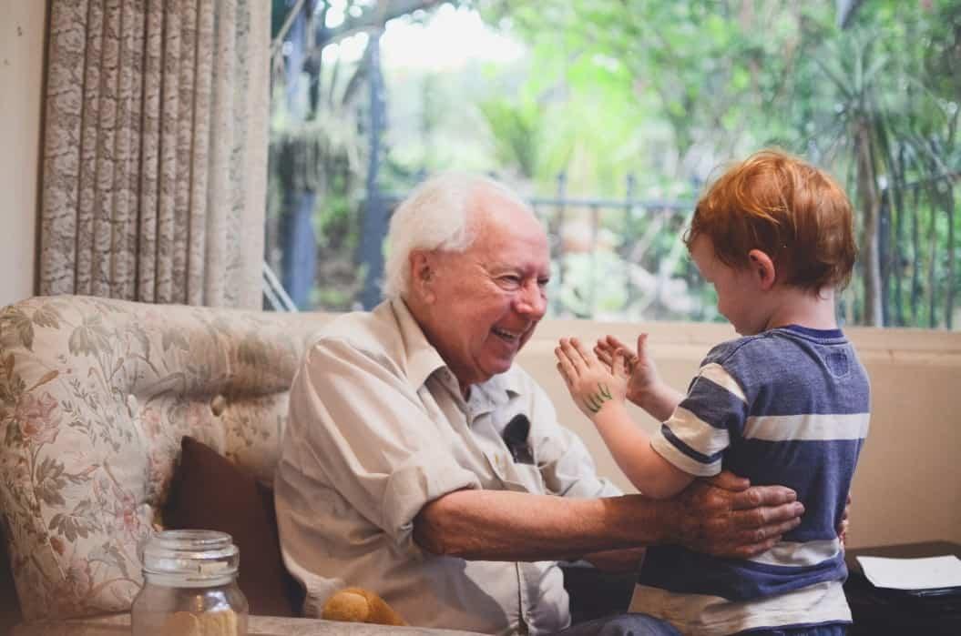 Grandparent smiling at his young grandson